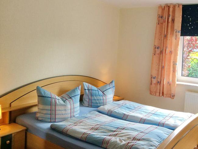 Ferienwohnung 2 - helles Schlafzimmer mit Doppelbett, Nachtschränken und Nachttischlampe
