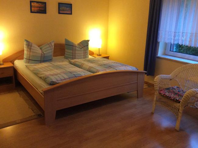 Ferienwohnung 4 - Schlafzimmer mit Doppelbett, Nachtschränken, Nachttischlampen und Stuhl