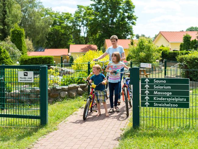 Frau mit 2 Kindern mit dem Fahrrad in der Ferienanlage
