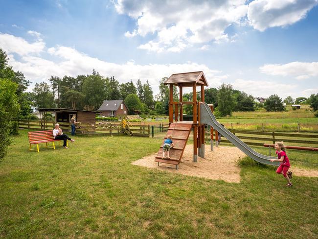 Spielplatz mit Kletterturm und Sandkasten und Streichelgehege