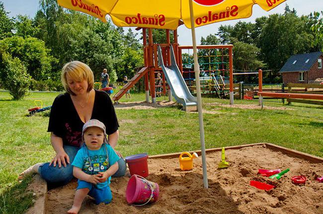 Mutter und Kind in der Sandkiste auf dem großen Spielplatz
