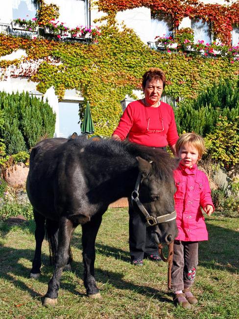 Mädchen und Frau mit einem Pony auf dem Reiterhof