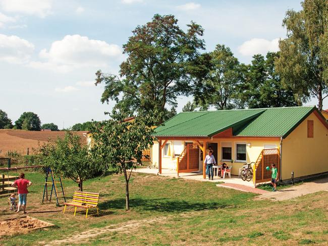 Blick auf unser Ferienhaus mit möblierter Terrasse und Spielplatz