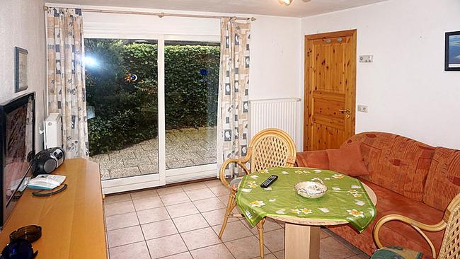 Ferienhaus - Wohnraum mit Sitzecke und TV