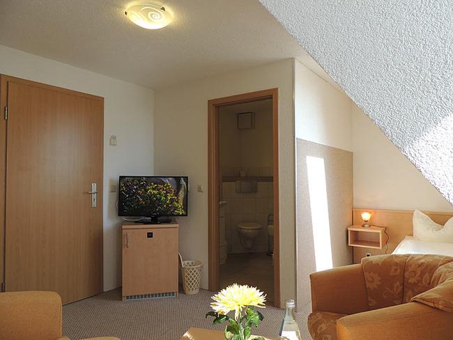 Einzelzimmer 11 Sessel und Fernseher