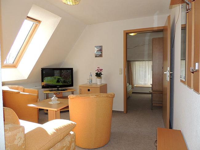 Appartement 7 Wohnraum mit Sessel und TV
