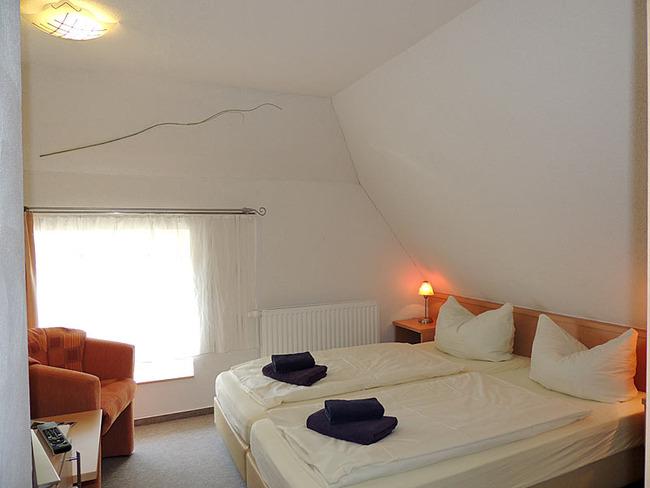 Doppelzimmer 8 mit Bett und Sessel