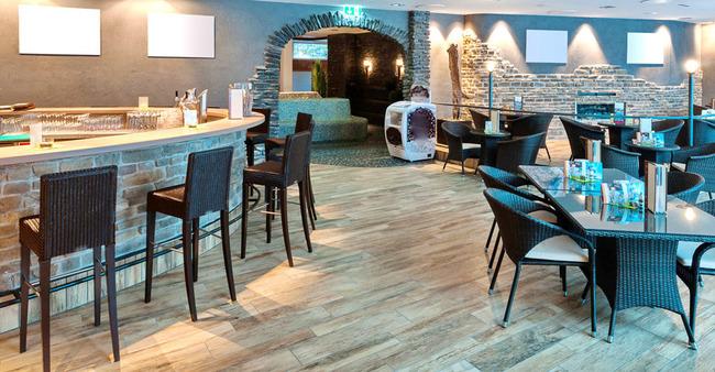Frühstücksraum mit Bar, mehreren Tischen und Lounge