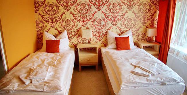 Zweibettzimmer mit Nachtschränken und Nachttischlampen
