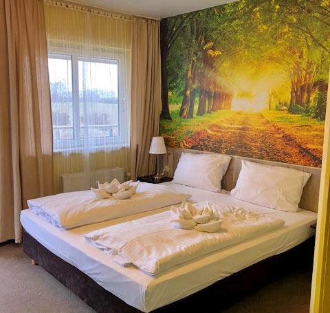 Doppelzimmer mit Nachtschränken, Nachttischlampen und Blick ins Grüne