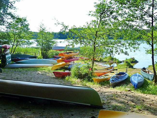 Kanus und Kajaks am Seeufer