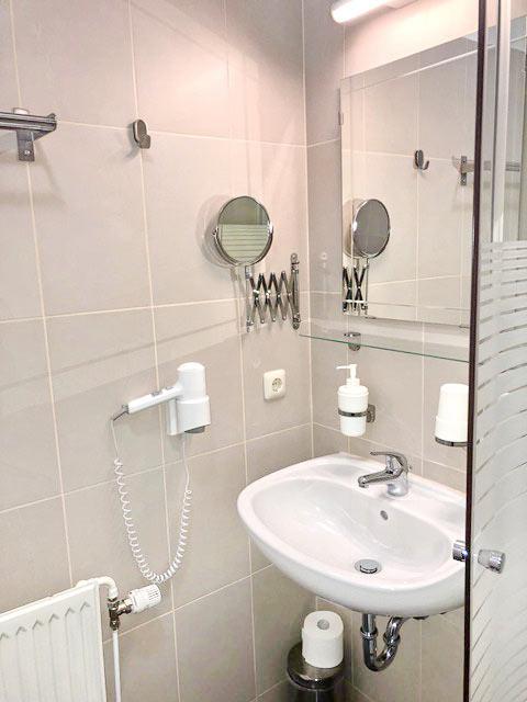 Badezimmer mit Dusche, WC, Waschbecken, Haartrockner, Kosmetikspiegel, großem Spiegel