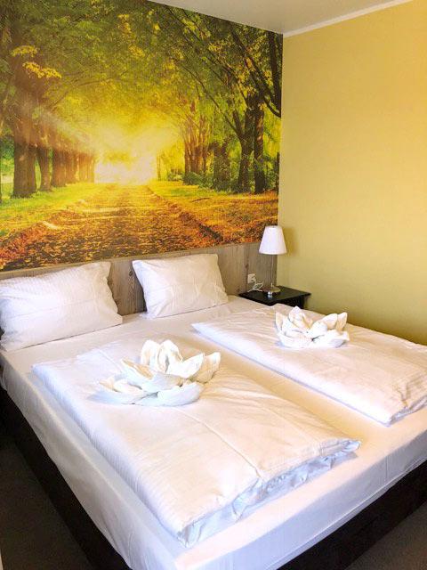 Doppelzimmer mit Bett, Nachtschränken und Nachttischlampen