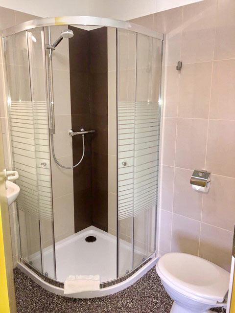 Badezimmer mit Runddusche, WC und Waschbecken