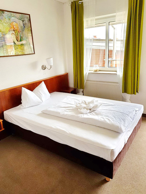 Einzelzimmer mit breitem Bett, Wandlampe, Nachtschränken