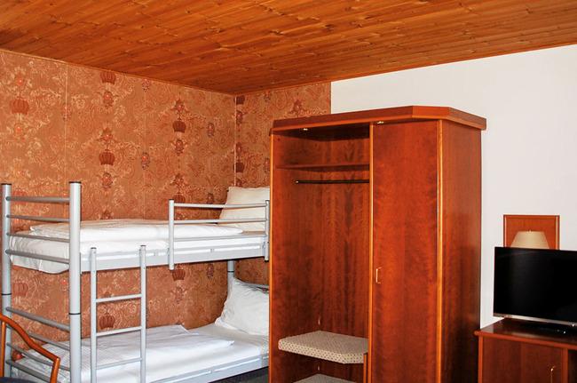 Zimmer mit Etagenbett, Kleiderschrank und TV