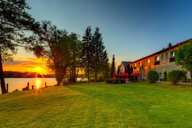 Sonnenuntergang - Außenansicht der Alten Schlossbrauerei mit Liegewiese, Terrasse und Mirower See