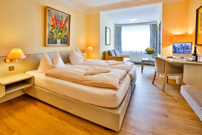 helles Doppelzimmer mit Bett und TV