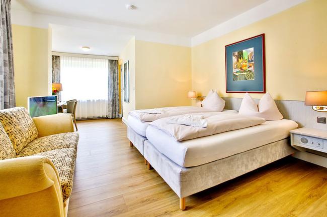 Doppelzimmer mit Couch und großem Doppelbett