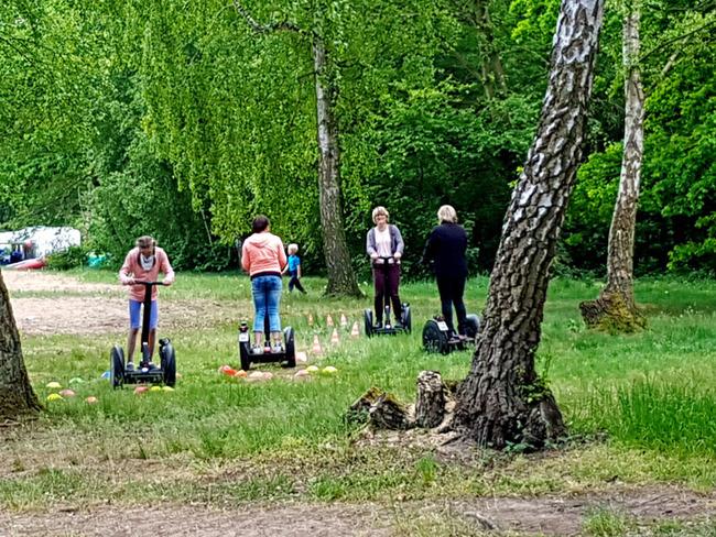 Teilnehmer auf einem Segway-Parcour im Grünen