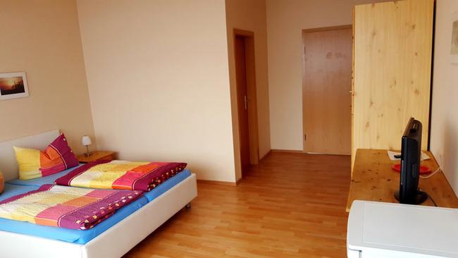 großzügig und hell eingerichtetes Zimmer mit Dusche, Twinbetten, TV, Kühlschrank, Kleiderschrank