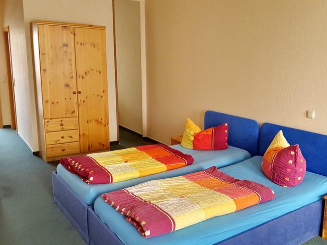 rustikal eingerichtetes Zimmer mit Twinbetten und Kleiderschrank