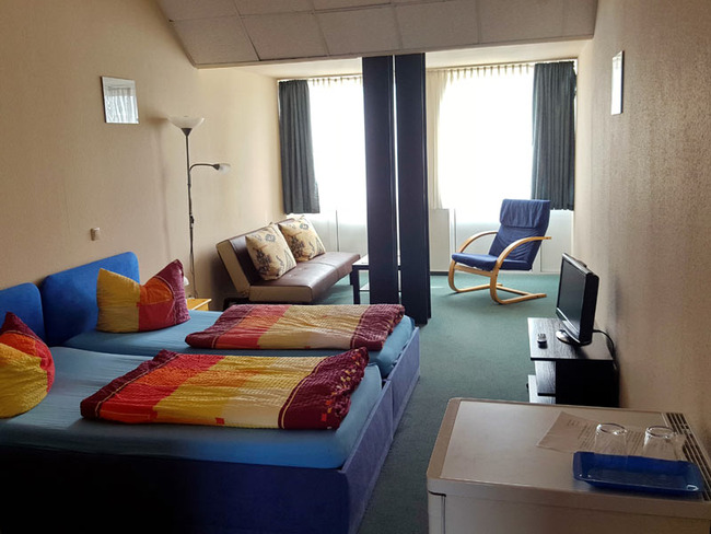 geräumiges Dreibettzimmer mit Twinbetten, TV, Kühlschrank, Couch und Relaxstuhl
