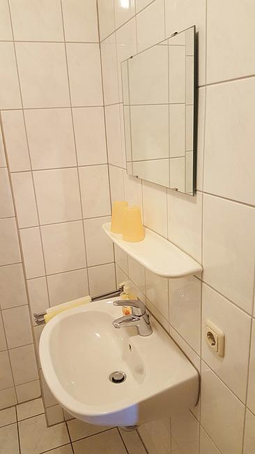 Bad mit Waschbecken und Spiegel