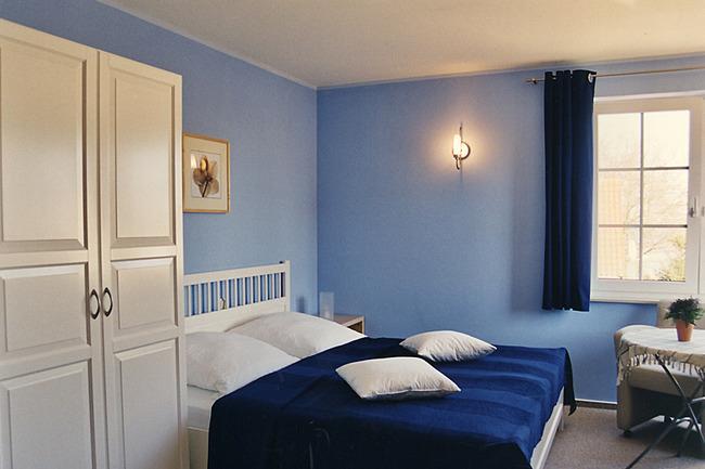 helles Doppelzimmer mit großem Bett und Sitzecke