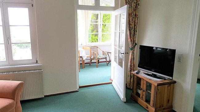 Wohnraum mit TV und Tür zur Loggia