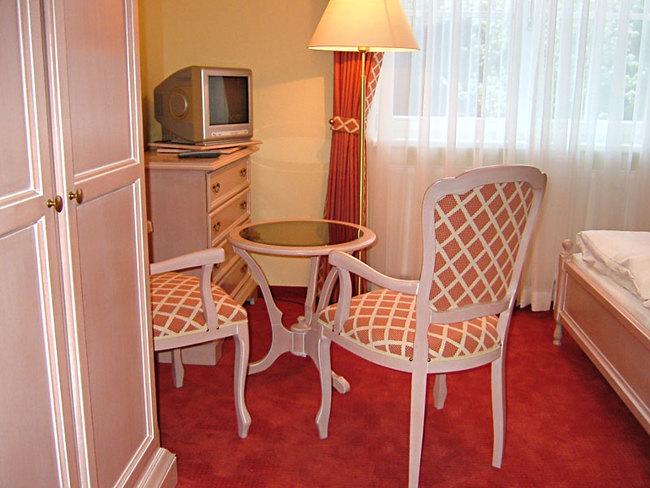 Pension - Zimmer mit Stühlen und TV