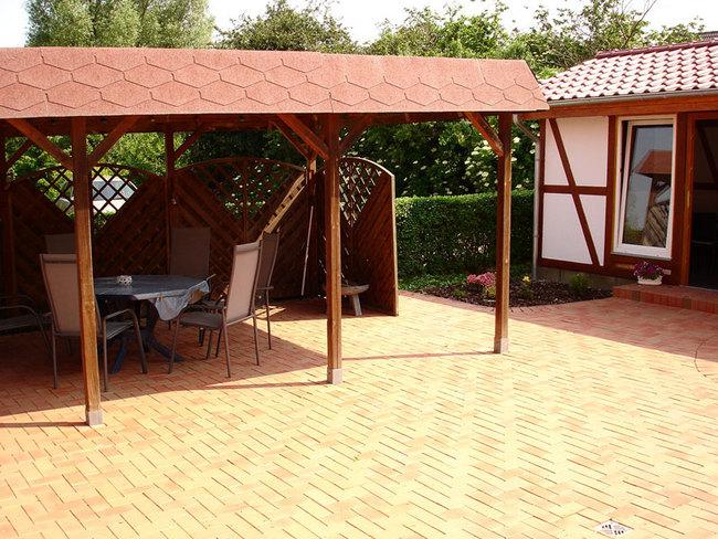 teilweise überdachte Terrasse mit Gartenmöbel