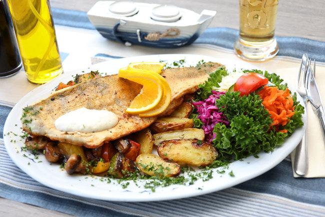 Fischgericht mit Kartoffelecken und Salat