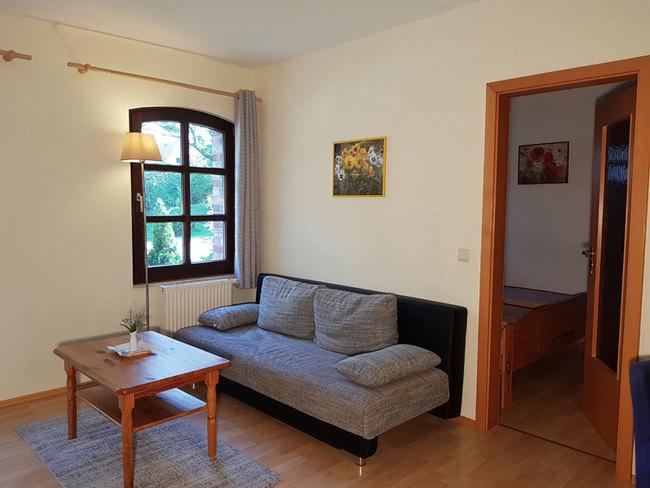 Fewo 5 - Wohnraum mit Couch und Tür zum SZ
