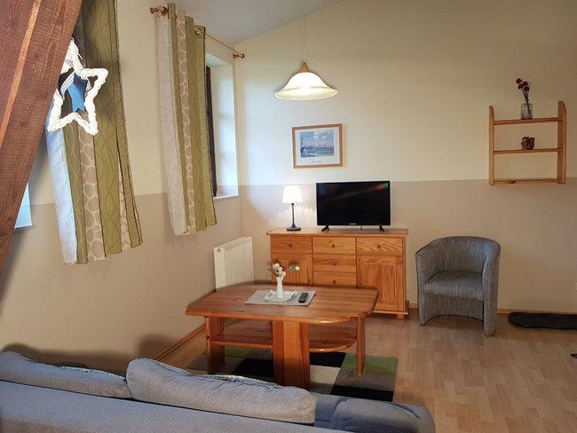 Fewo 7 - Wohnbereich mit Couch, Sideboard und TV