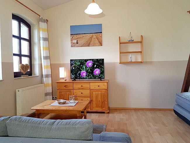 Fewo 10 - Wohnraum mit Couch, Sideboard und TV