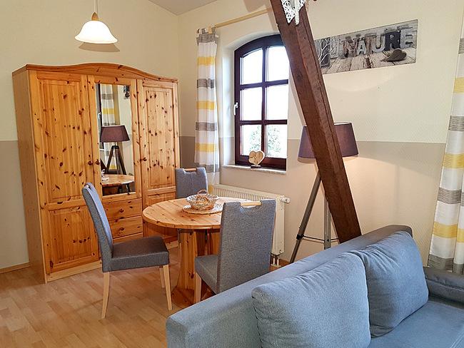 Fewo 10 - Wohnraum mit Couch, Essplatz und Schrank